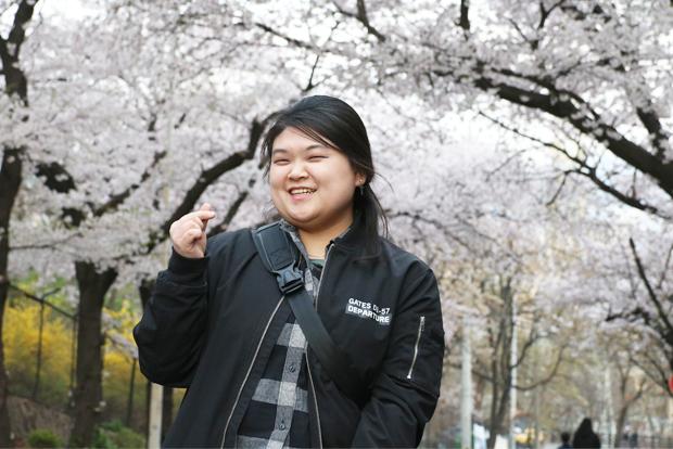 벚꽃이 흐드러진 회사 앞에서 활짝 웃고 있는 한혜인 기부자