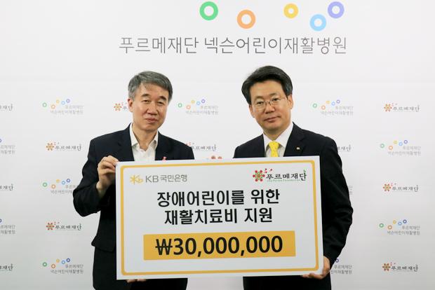 백경학 푸르메재단 상임이사에게 구승열 KB국민은행 상품본부장(오른쪽)이 장애어린이 재활치료비 3천만 원을 전달했다.