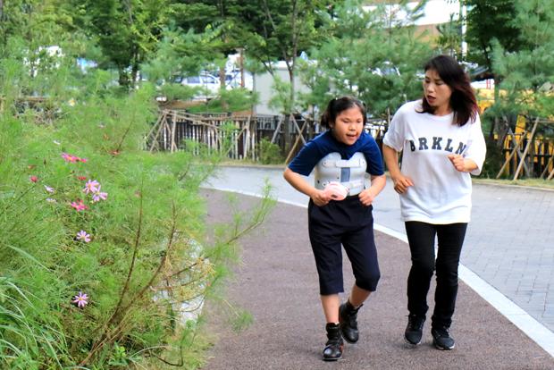맞춤용 교정신발을 신고 걷기 연습을 하고 있는 장선우 어린이와 엄마 박미정 씨