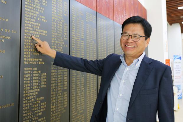 푸르메재단 기부벽에서 자신의 이름을 가리키며 활짝 웃고 있는 오산택 대표
