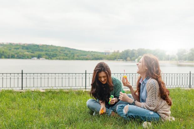 풀밭에 앉아 시간을 보내고 있는 두 자매