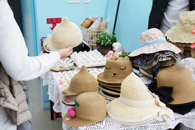 푸르메마켓에 나온 각양각색 모자를 살펴보고 있는 병원 이용자