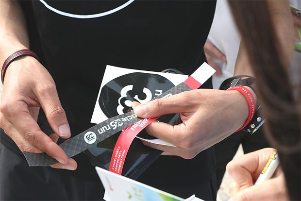 미라클365런의 증표인 '365' 스티커를 받고 있는 참가자
