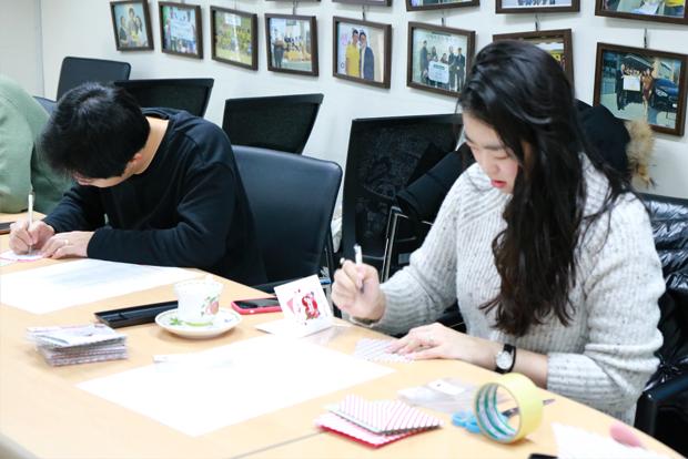 장애어린이와 가족들에게 손 편지를 쓰고 있는 현대모비스 임직원들