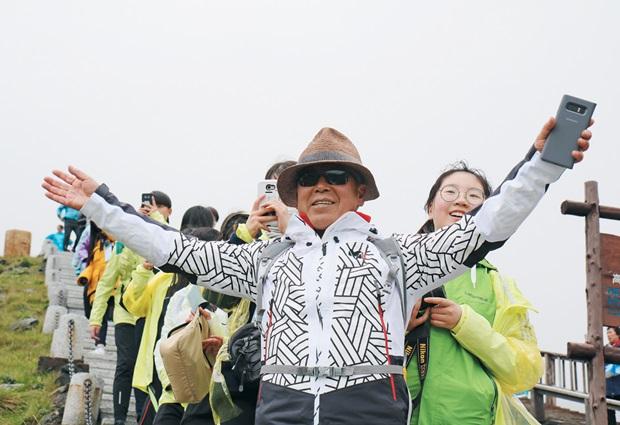지난달 28일 백두산에 오른 엄홍길 대장과 아이들. 이날은 날씨가 흐려 천지의 모습을 제대로 보지 못했다. 푸르메재단 제공.
