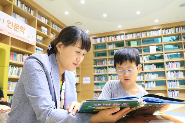 아들 두민이가 최고로 꼽는 장소인 어린이도서관에서 책을 읽고 있는 황혜진 씨
