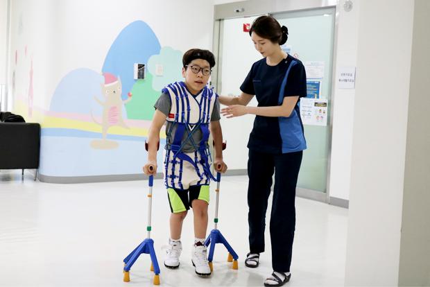 집중운동치료 때 지팡이를 짚고 걷는 연습을 하는 주언이