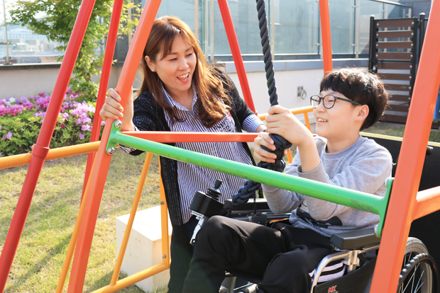 엄마 옆에서 휠체어 그네를 타고 있는 장태환 어린이.