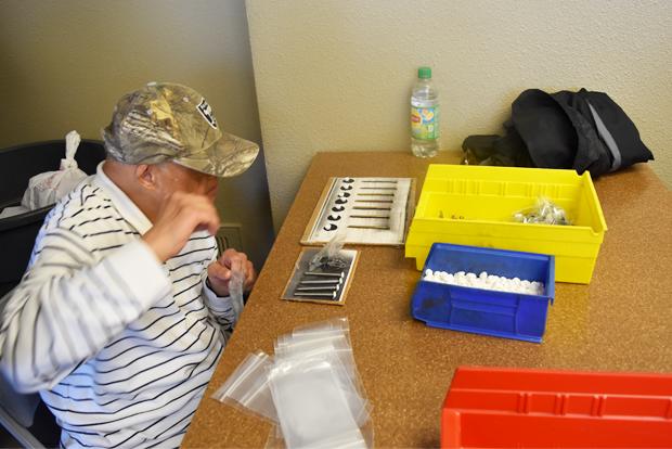 샘플 그림판에 부품을 올려놓고 개수를 확인하는 근로자