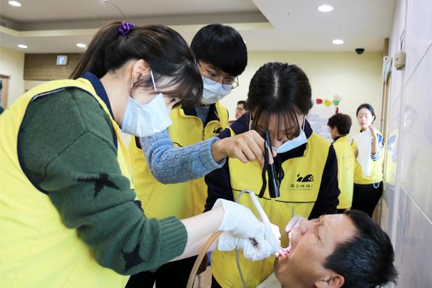중증장애인 치과진료를 돕고 있는 김성재 학생(가운데)