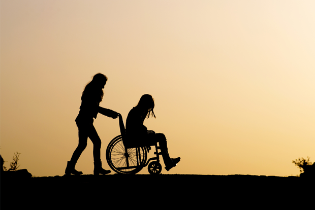 휠체어에 앉아 있는 여성과 끌어주는 여성