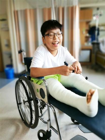 무릎 관절 수술 후 휠체어를 타고 있는 주언이(이주언 가족 제공)