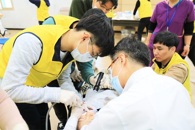 치과의사 옆에서 석션을 맡은 윤석헌 학생(왼쪽)
