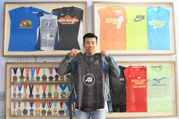 70여 개 대회의 증표 앞에서 365명의 이름이 적힌 티셔츠를 들고 웃고 있는 션 홍보대사.