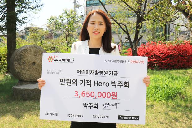 자신의 서명을 남긴 기부보드를 들고 기념사진을 촬영한 박주희 기부자.