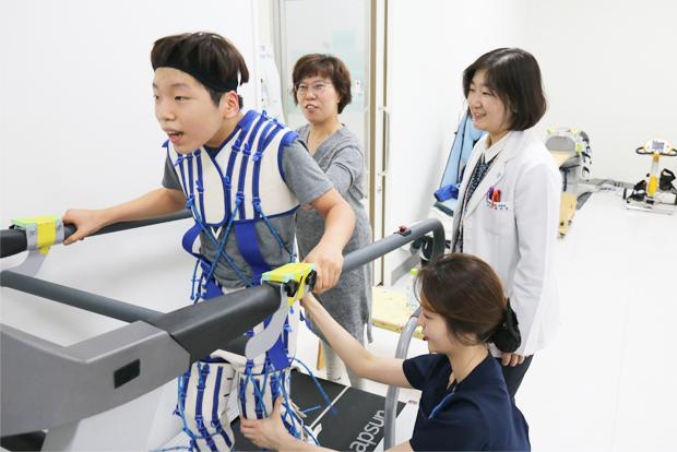 환아‧보호자‧의료진과의 호흡이 중요한 집중운동치료. 테라슈트를 입고 속도를 높여가며 보행 연습을 하는 모습.