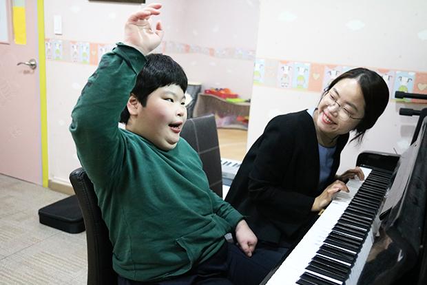 음악치료사의 피아노 연주에 맞춰 노래를 부르고 있는 지우